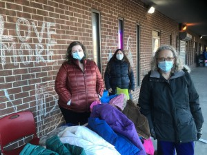 (from left) Victoria Palmatier, Michelle Lipar, and Irene Blean hand out free winter coats at Barbour Library