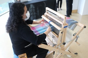 Ana Cuevas works on a scarf during the opening of the Hartford Artisans Weaving Center exhibit at the Hartford Public Library Downtown on Thursday, Sept. 9.