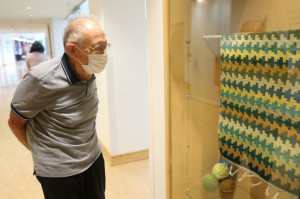 Garrett Weaver admires a rug he created at the Hartford Artisans Weaving Center during the opening of the center's Perspectives on Color exhibit at the Hartford Public Library Downtown on Sept. 9, 2021.
